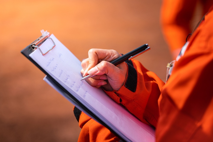 a workers is making notes on a clipboard