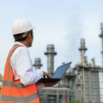 an industrial worker wearing a hard hat and orange reflective vest surveys an energy plant in the distance