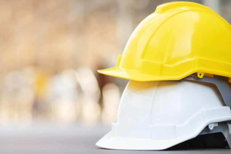 A yellow hard hat stacked on top of a white hard hat.