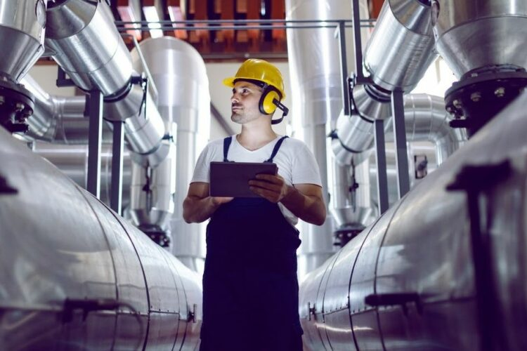 A man wearing a hard hat and protective ear muffs surveys equipment in an industrial plant.