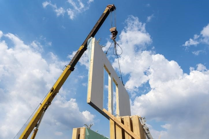 A crane lifting the wall of a modular building during construction.